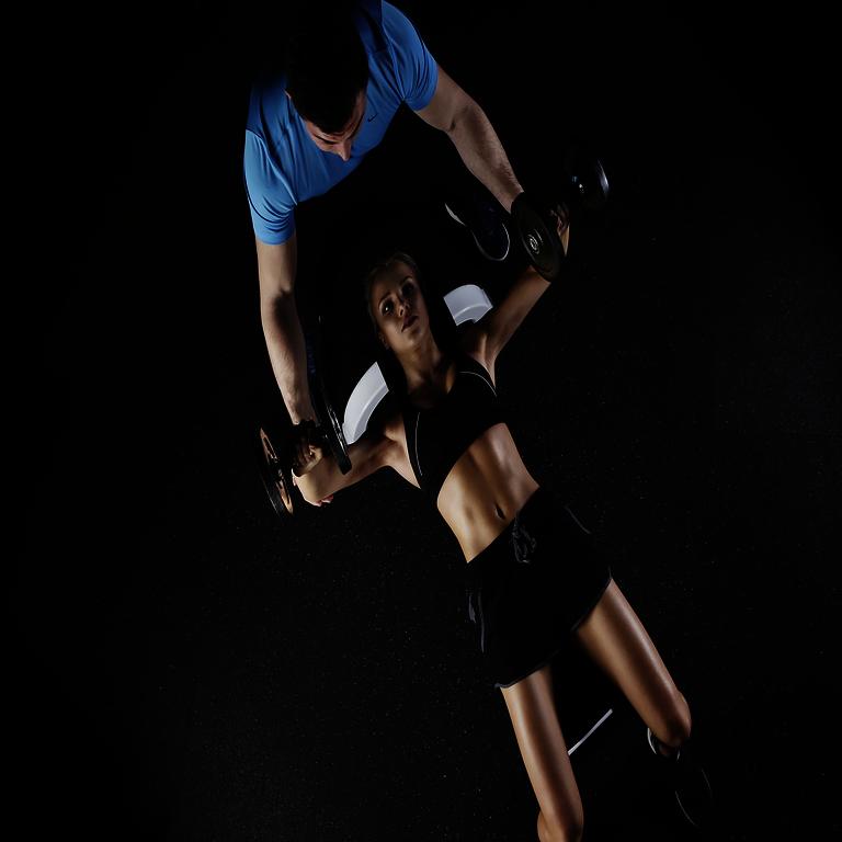 Durchführung des Krafttrainings - Frau in Rückenlage auf der Trainingsbank und Kurzhanteln in den Händen wird vom Trainer assistiert