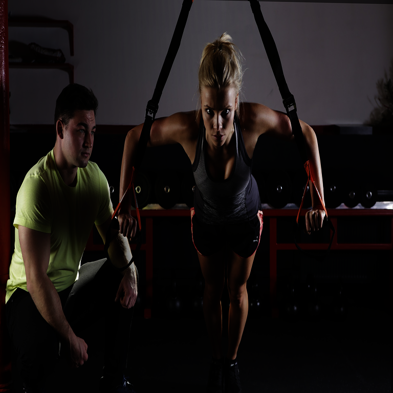 Optimierung des Krafttrainings - Frau in Trainingsgewand mit Trainer