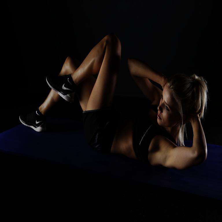 Bodyweight - Frau in Rückenlage mit Trainingsgewand berührt mit einem Ellbogen das gegenüberliegende Knie
