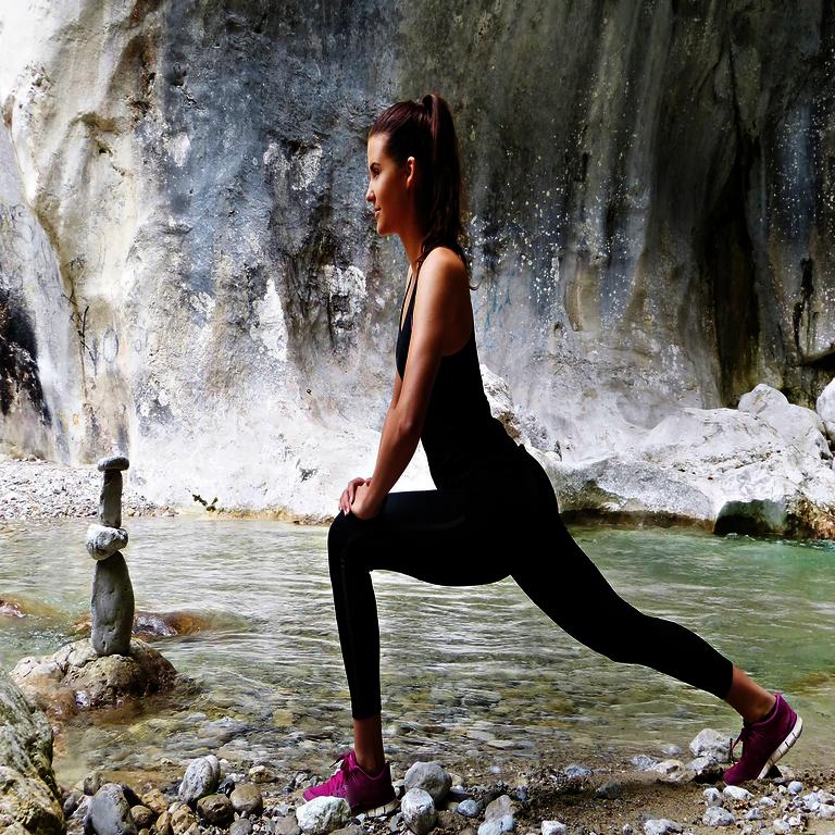 Warm Up - Frau vor Wasser und Felsen in Trainingsgewand in Dehnposition der Beine