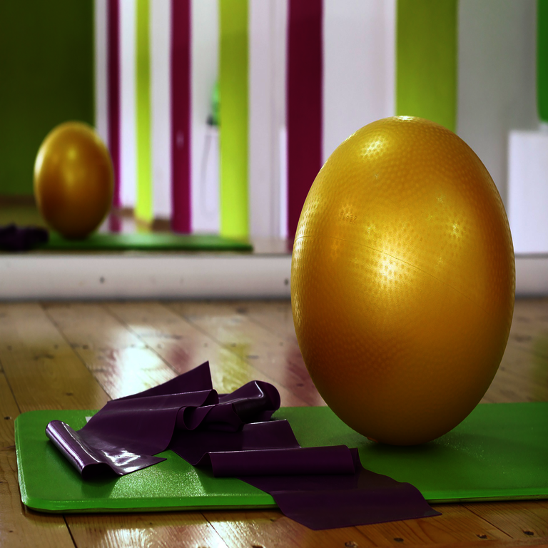 Trainingsutensilien - grüne Trainingsmatte, lila Zuband und gelber Swiss-Ball