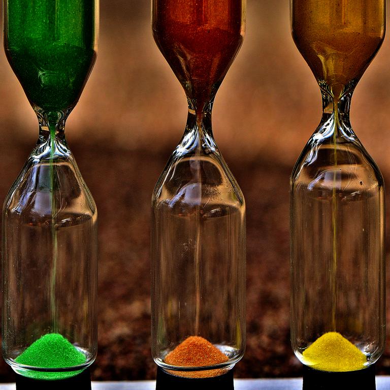 Belastungsnormative - drei Sanduhren aus Glas mit grünem, rotem und gelbem Sand