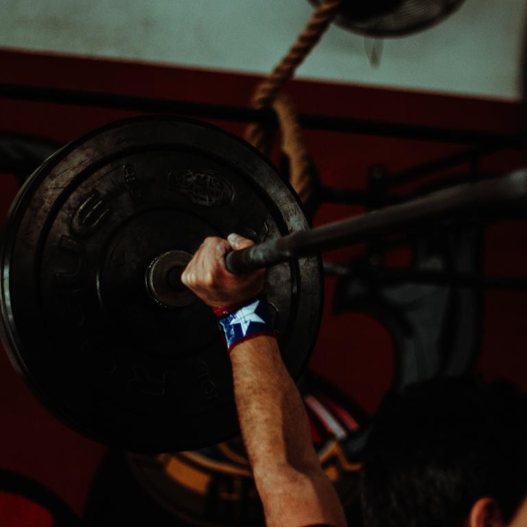 Fitness- und Krafttrainingsübungen - Mann stemmt eine Langhantel