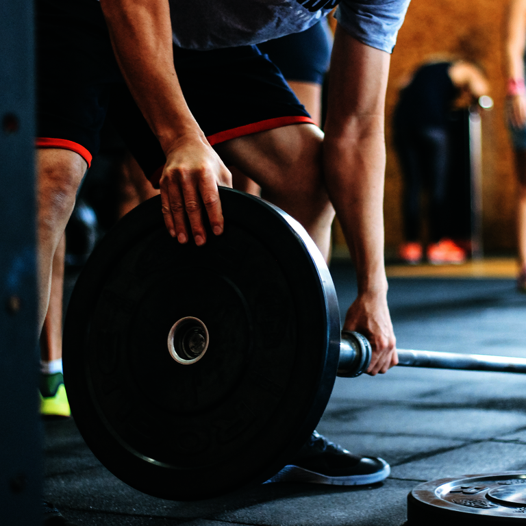 Wichtige Muskeln für das Training - Unterkörper von Mann, eine Hand hält die Langhantelstange, die andere steckt eine große Gewichtsscheibe an