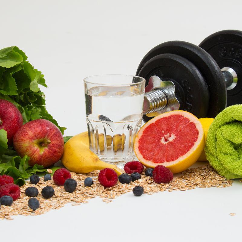 Effektives Training - Hantel mit Wasserglas, Apfel, Banane, Haferflocken, Beeren