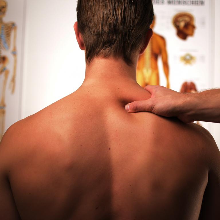 Training und die Auswirkungen auf den Körper - Rücken von Mann dem mit einer Hand im oberen Bereich der Trapezmuskel massiert wird