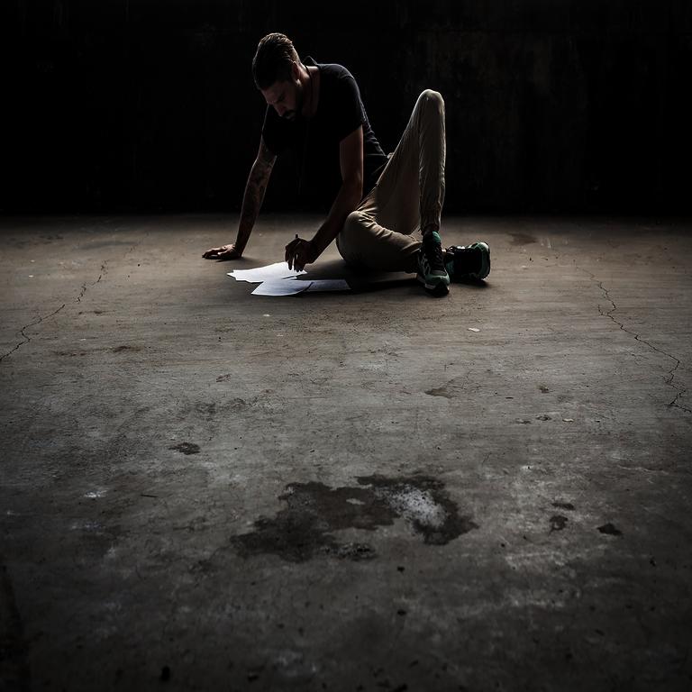 Trainingsprinzipien - Mann mit Zetteln und Stift sitzend auf einem Betonboden